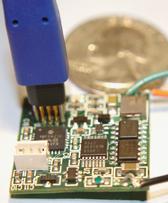 TC2030-NL tiny footprint debug connector inserted into mircrocomputer  PCB